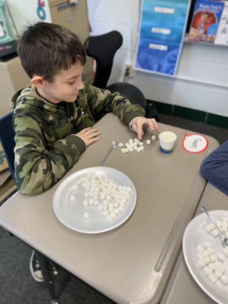 Using spoons to pick up marshmallows.